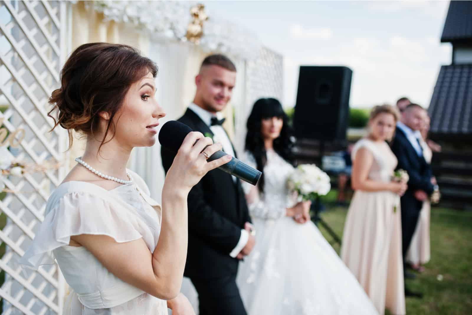 Rede des Zeremonienmeisters auf dem Hochzeitspaar des Mikrofonhintergrunds