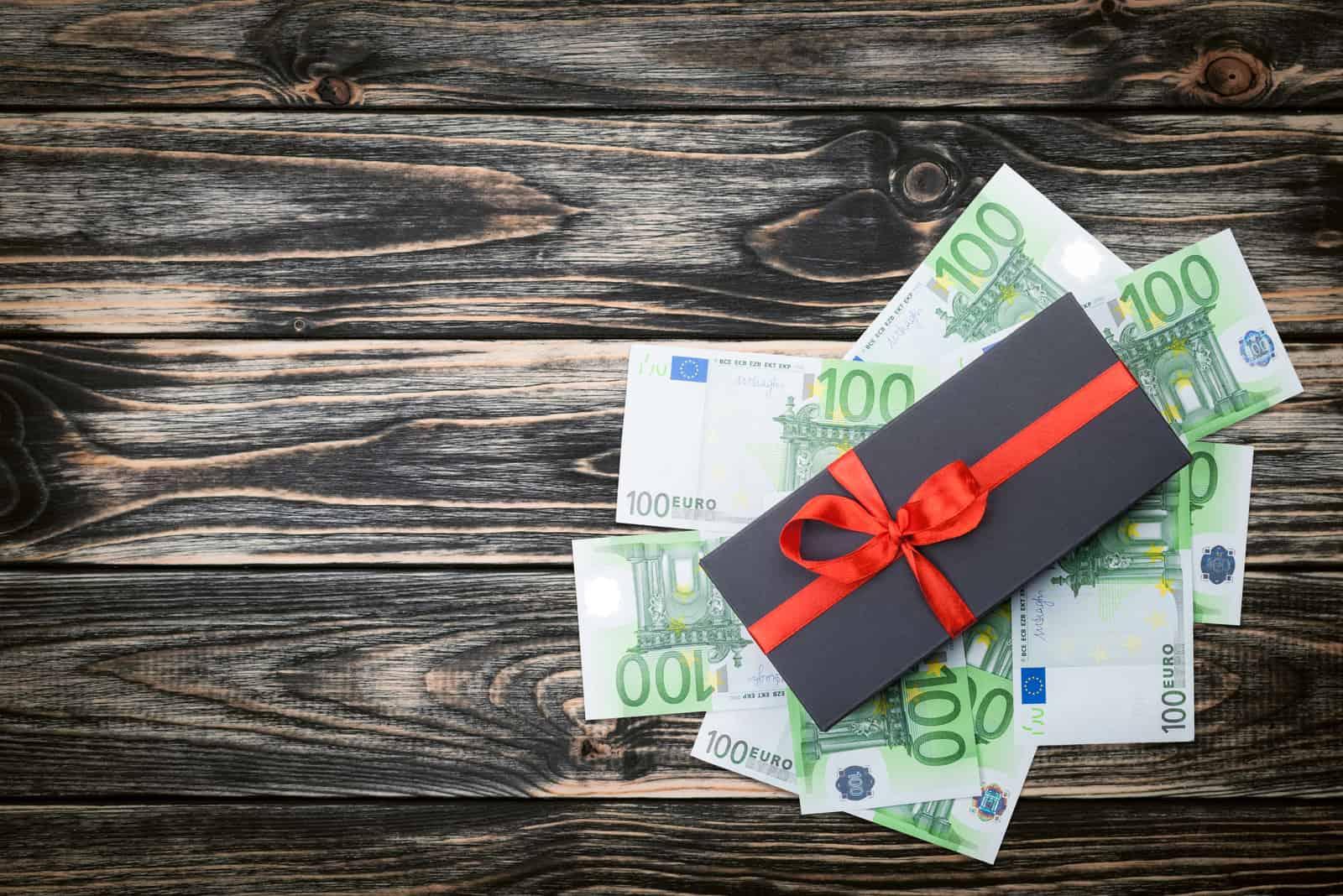Schwarze Geschenkbox mit Schleife mit Euro-Banknoten auf einem Holztisch. Draufsicht, Kopierraum