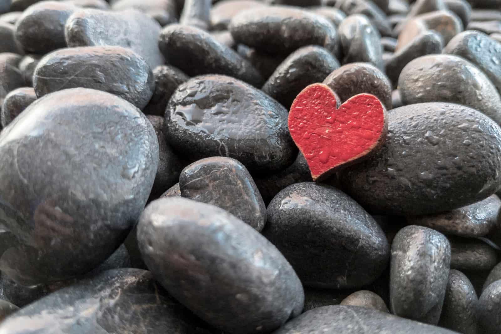 Strandsteine mit Wassertropfen und rotem Herzen
