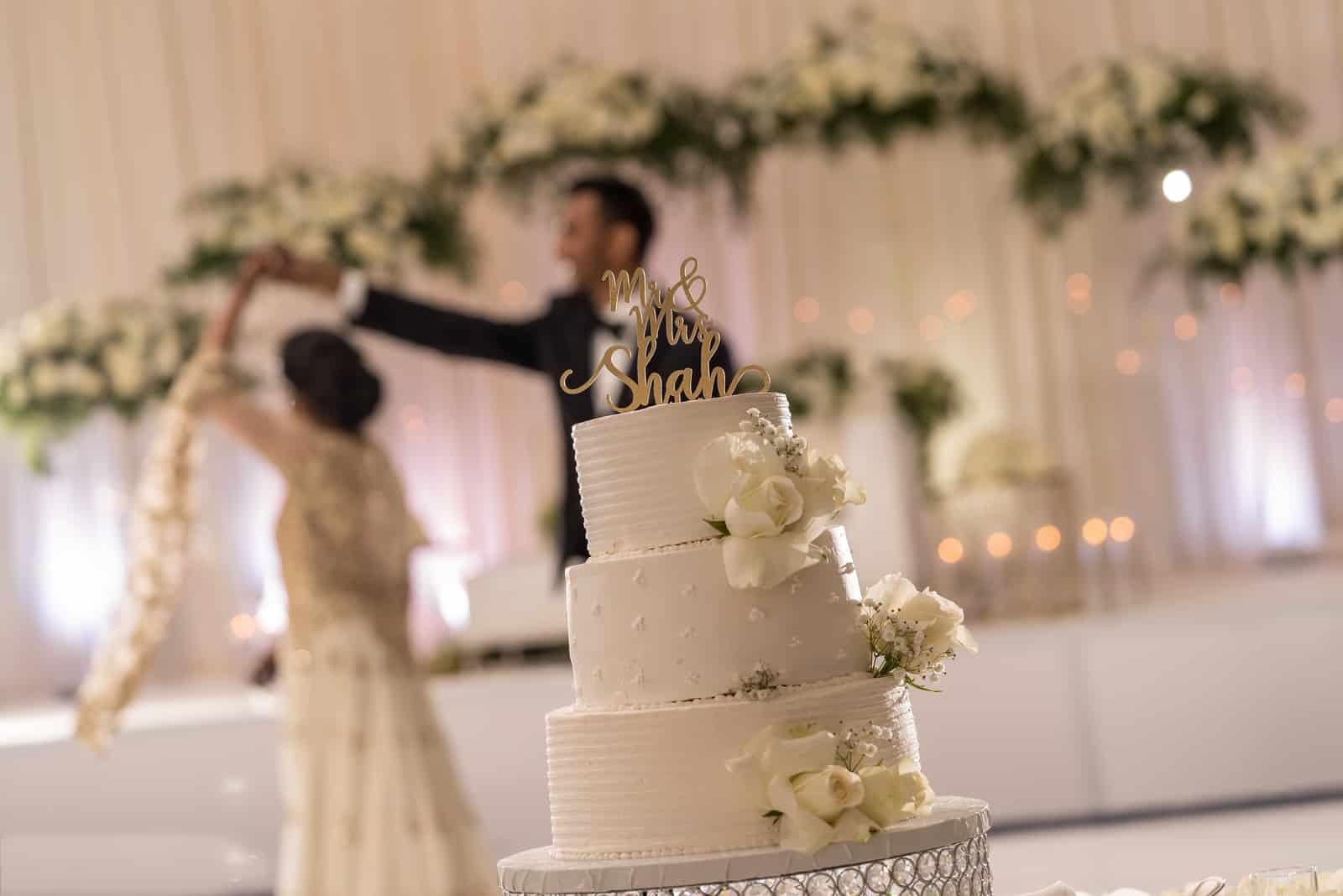 Vor einer weißen schönen Hochzeitstorte tanzen die Jungvermählten