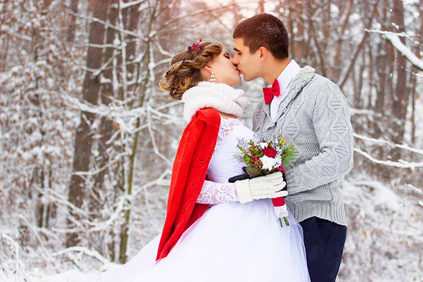Winterhochzeit, Jungvermählten küssen sich im Wald