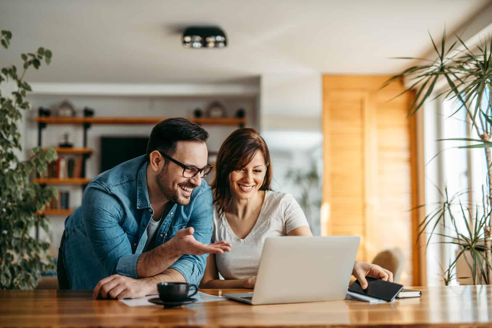 ein lächelndes Paar, das Kaffee trinkt und etwas auf einem Laptop betrachtet