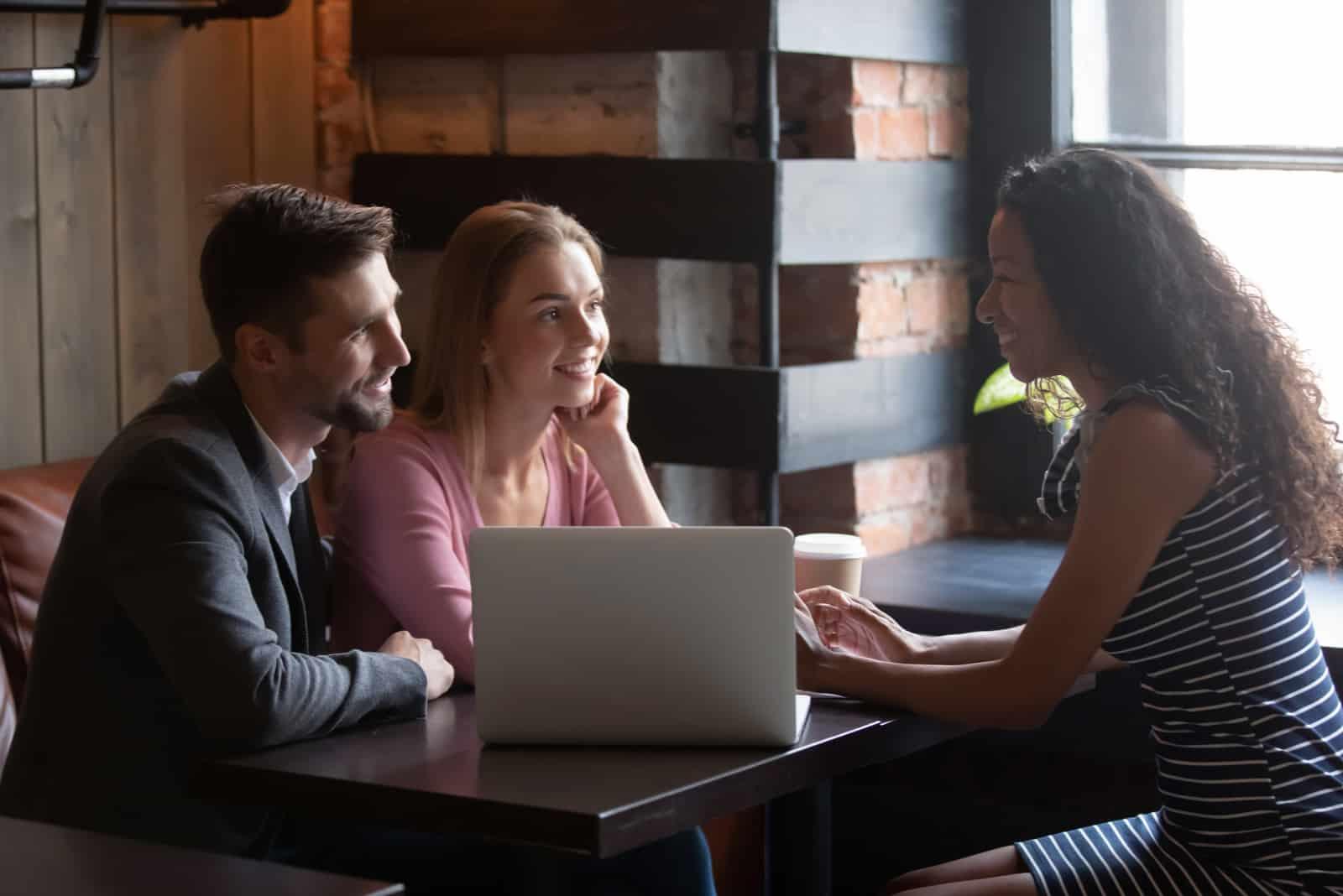 ein liebendes Paar, das mit einer Frau in einem Café spricht
