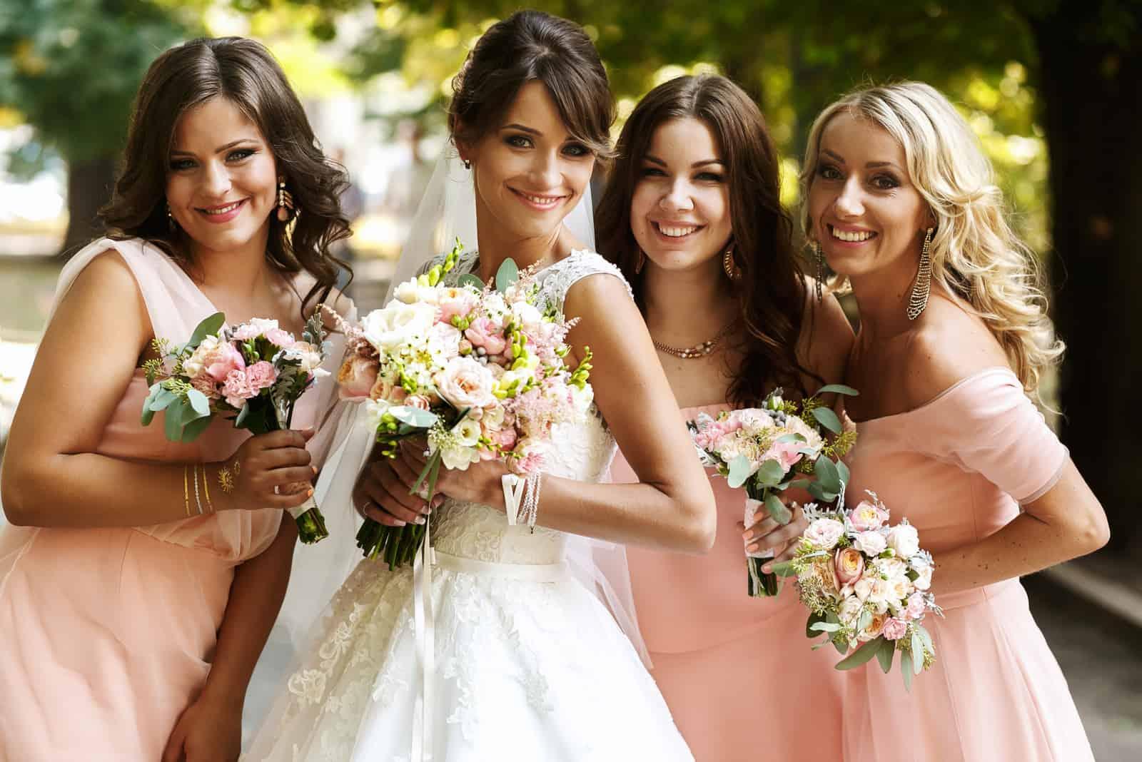 eine Braut mit drei Brautjungfern im Park