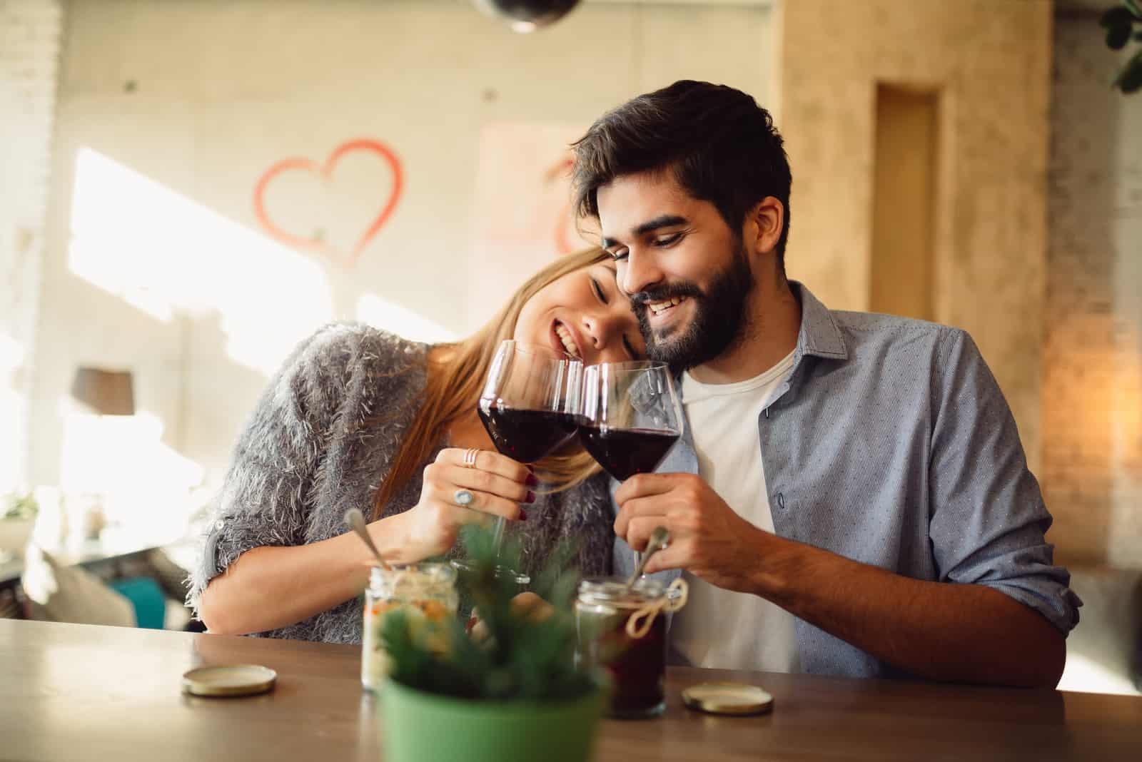 glückliches Paar an der Bar trinkt Wein