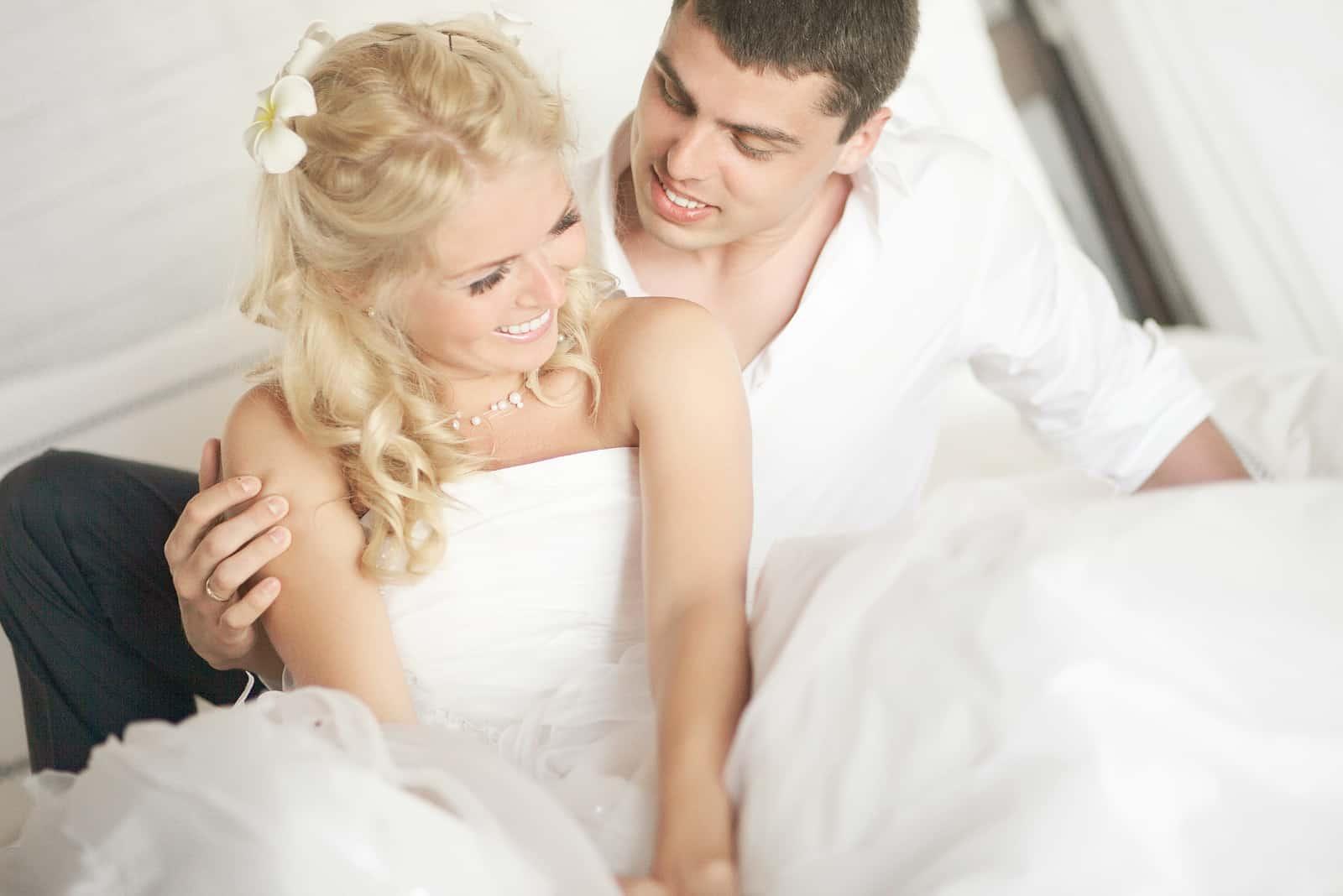 lächelnde Jungvermählten umarmen sich im Bett