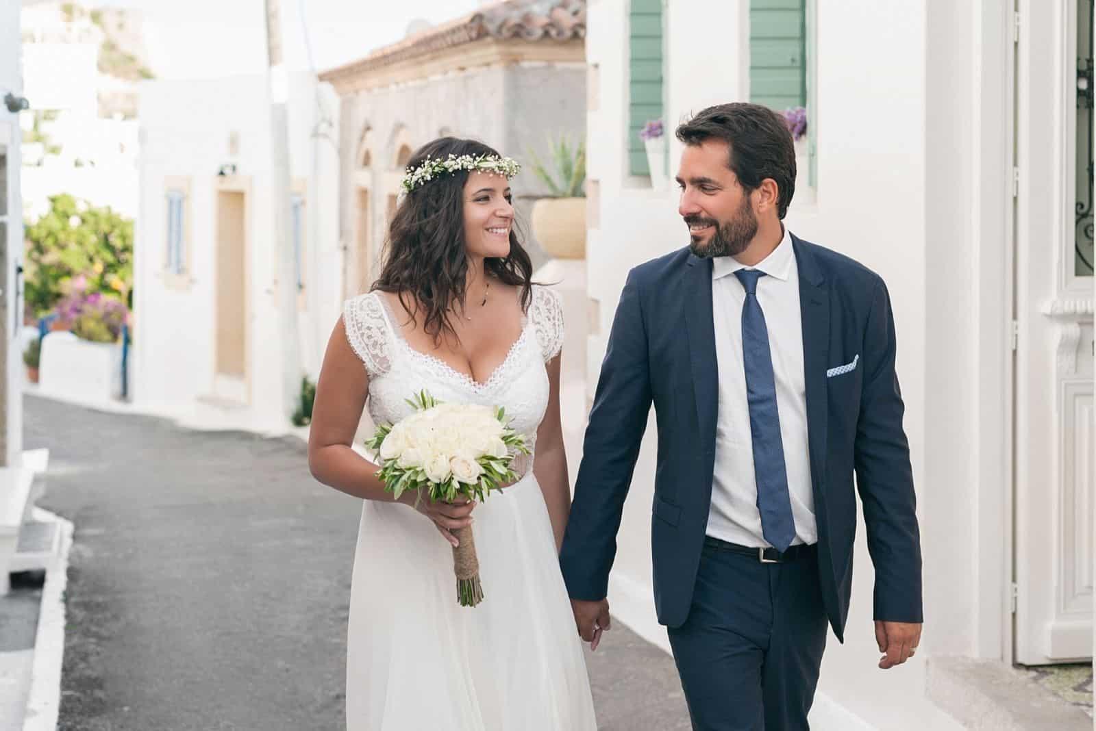 lächelnde schöne Jungvermählten gehen die Straße entlang