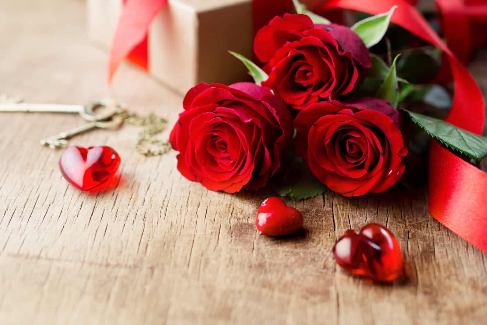 rote Rosen, Geschenk und rote Herzen Dekor auf dem Tisch