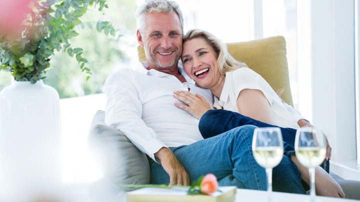ein glückliches altes Ehepaar sitzt im Wohnzimmer und umarmt sich