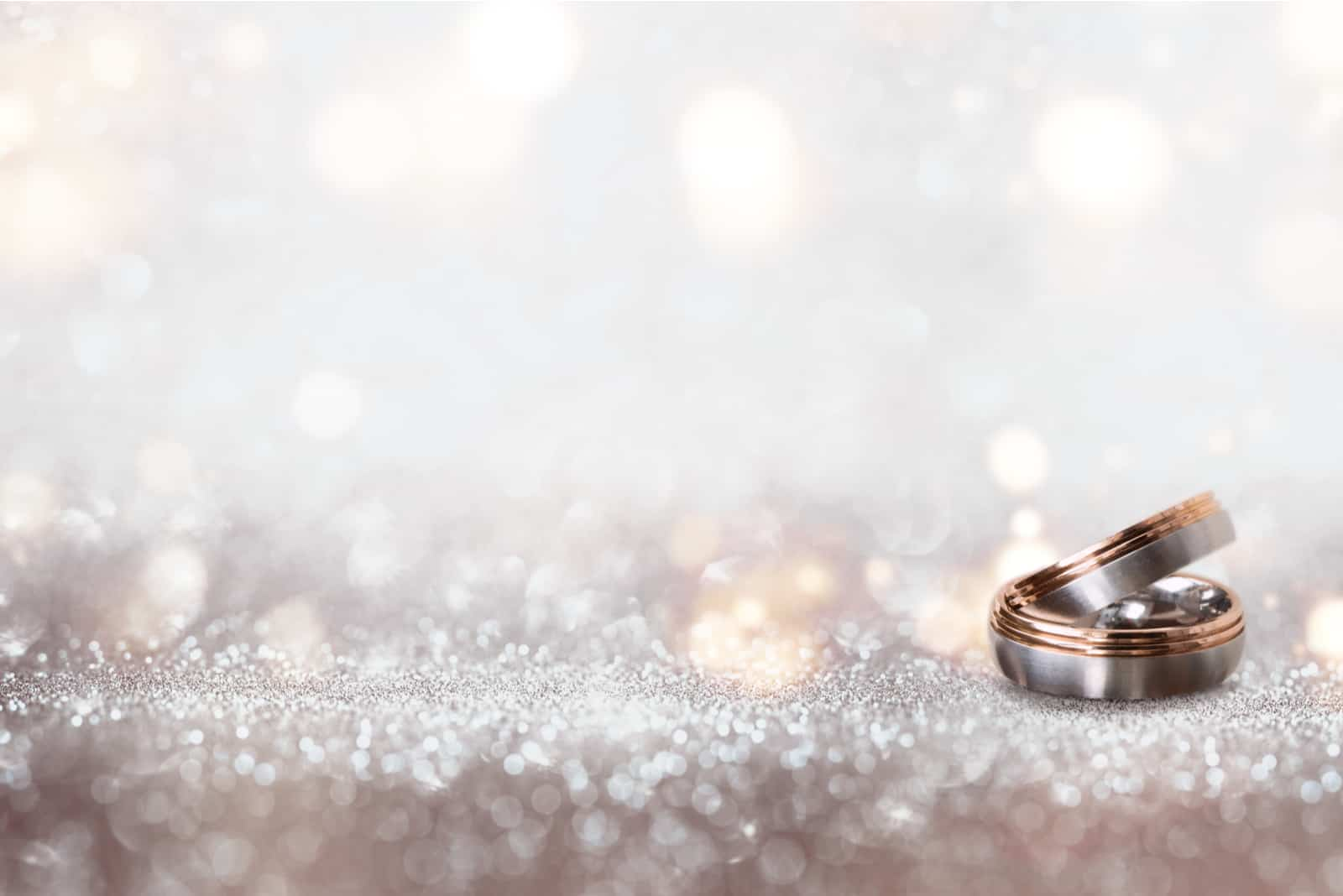 Abstrakter silberner Glitzer-Bokehhintergrund mit Eheringen für eine Einladung