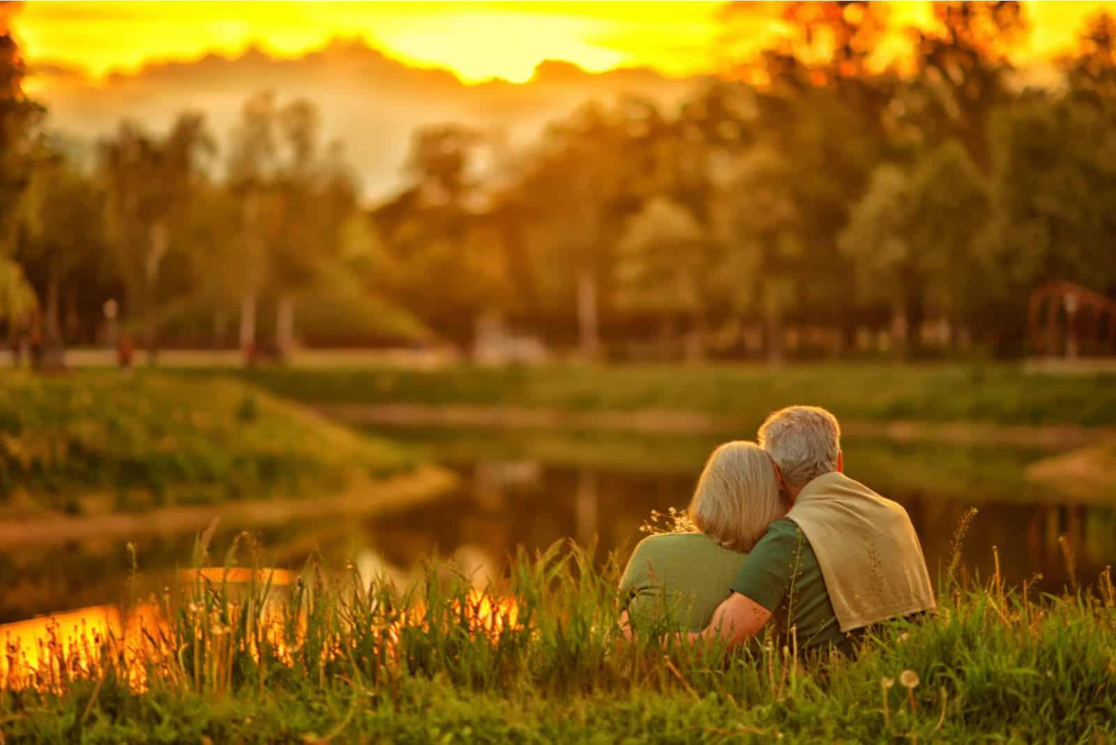 Bei Sonnenuntergang am Ufer des Sees umarmt sich ein älteres Ehepaar