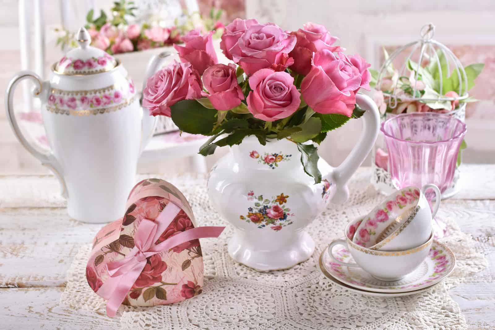 Blumenstrauß aus rosa Rosen im Porzellankrug auf dem Tisch mit herzförmiger Geschenkbox und Porzellan im Shabby-Chic-Interieur