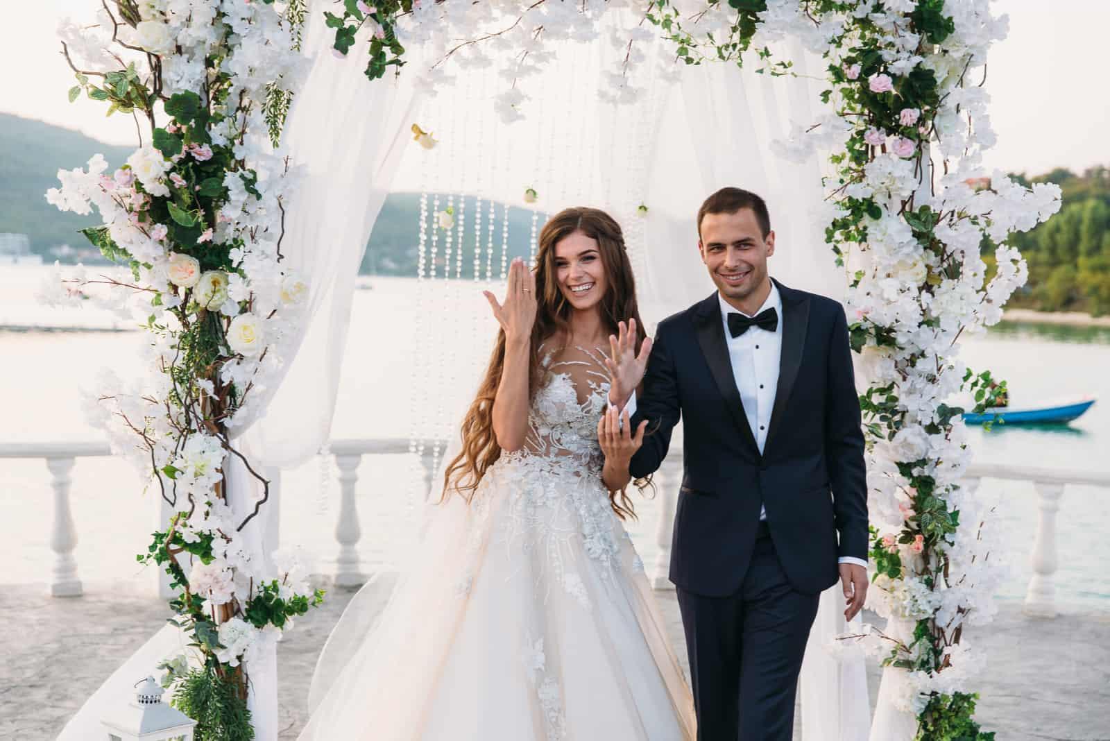 Bräutigam und Braut bei der Hochzeitstagzeremonie mit Bogen auf Hintergrund
