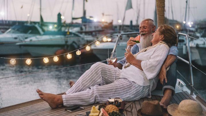 Ein älteres Liebespaar isst Obst und trinkt Champagner auf einer Yacht
