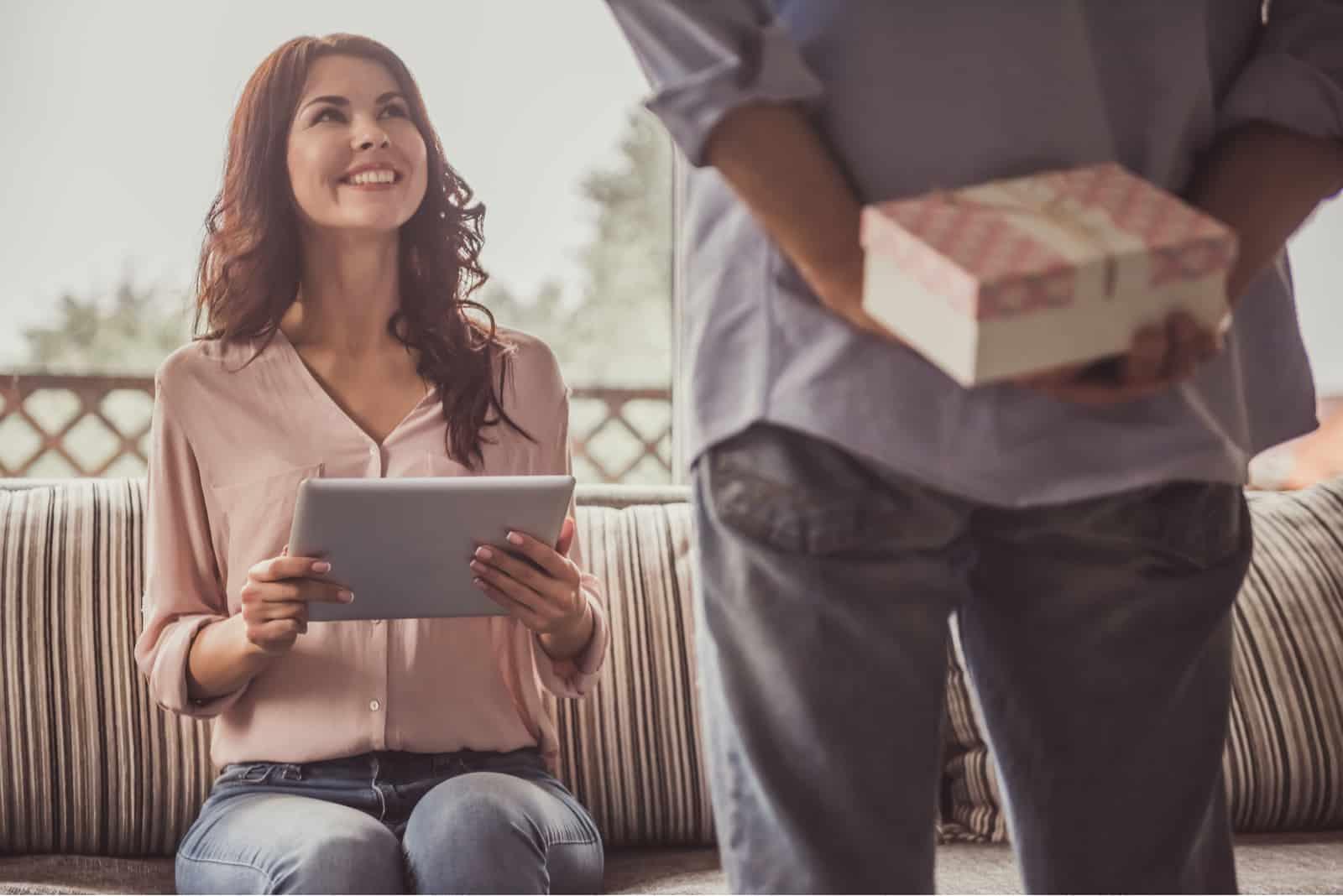 Ein Mann versteckt hinter seinem Rücken ein Geschenk für eine lächelnde Frau, die mit einer Tablette in den Händen auf einem Sofa sitzt