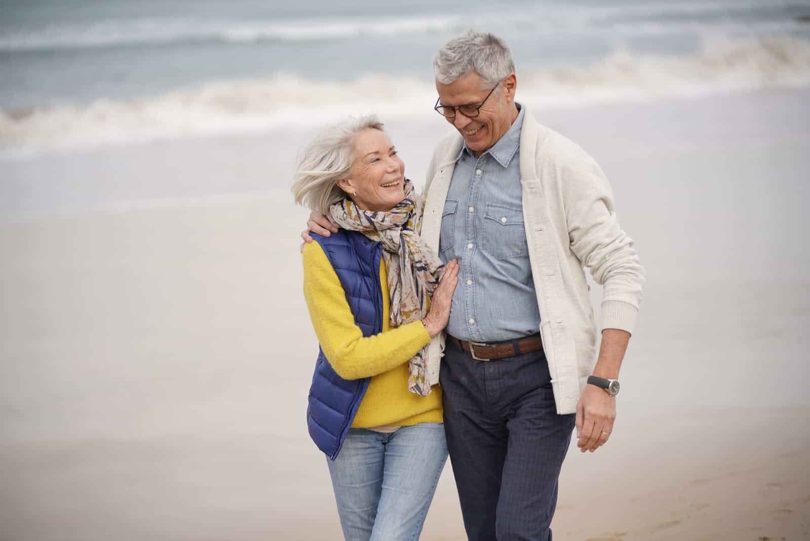 Ein älteres glückliches Paar geht am Strand entlang