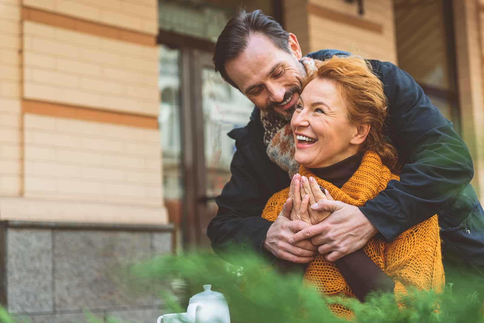 Ein bärtiger Mann umarmt eine lächelnde Frau von hinten