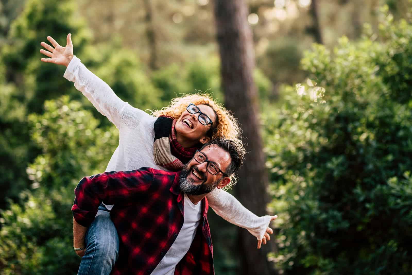Ein glückliches Paar hat Spaß im Wald
