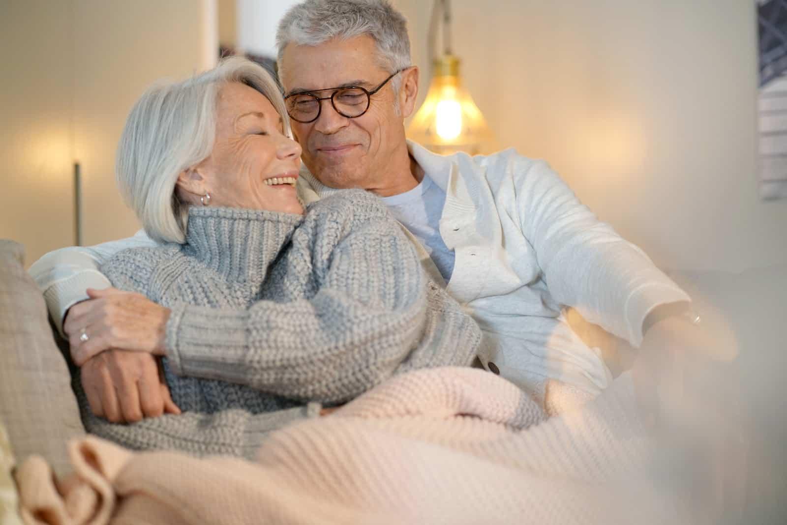 Ein glückliches älteres Ehepaar sitzt auf einem Sofa und umarmt sich
