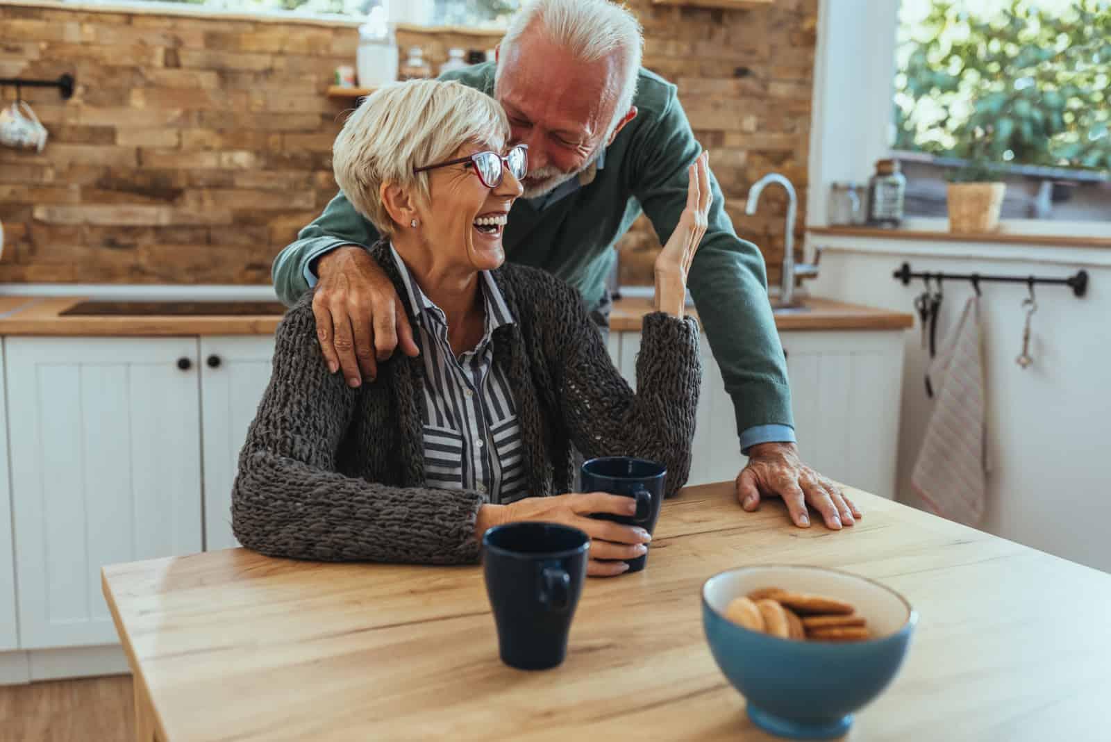 Ein lächelndes älteres Ehepaar umarmt sich in der Küche