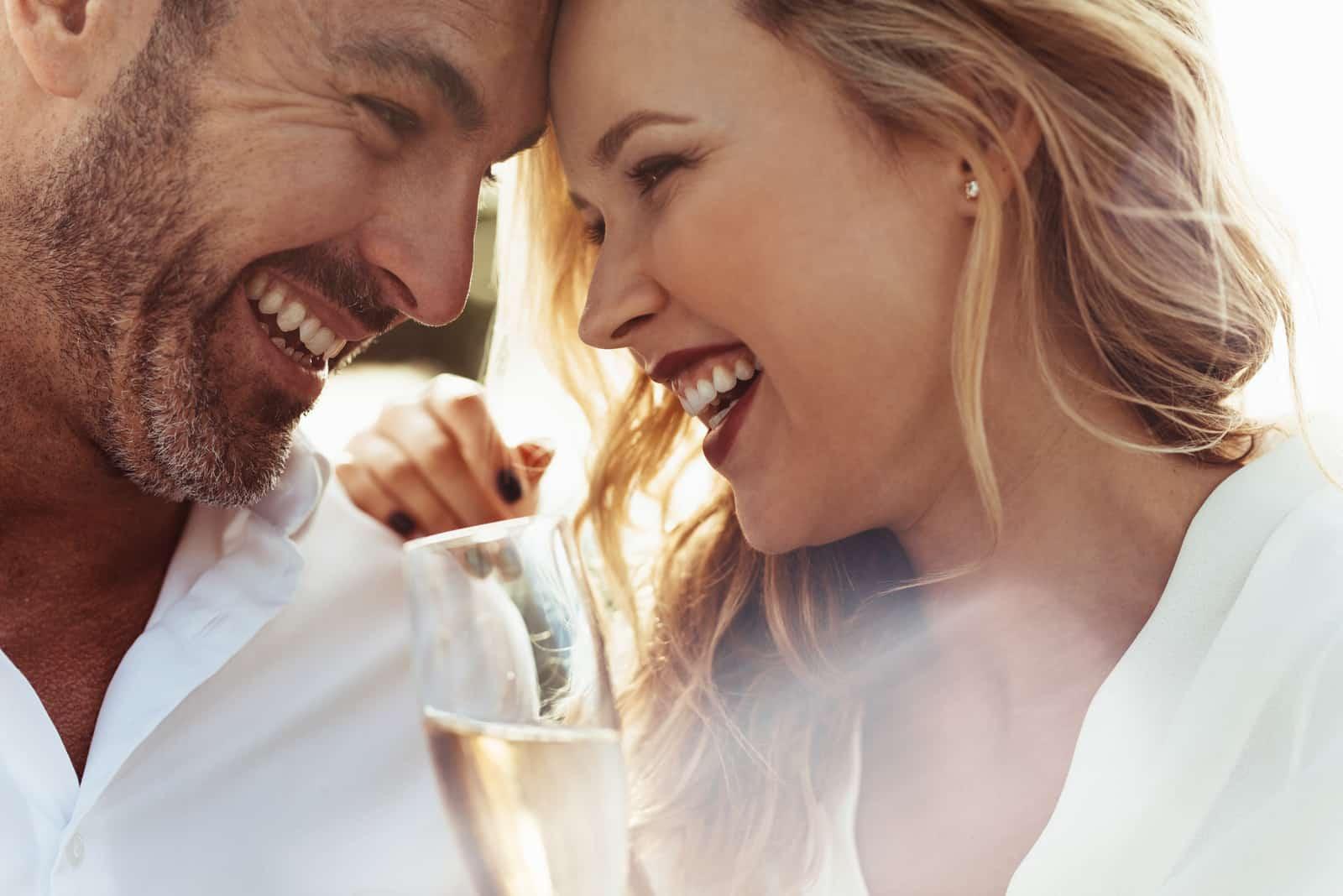 Ein liebevolles Paar, das sich umarmt und Spaß mit Champagner hat