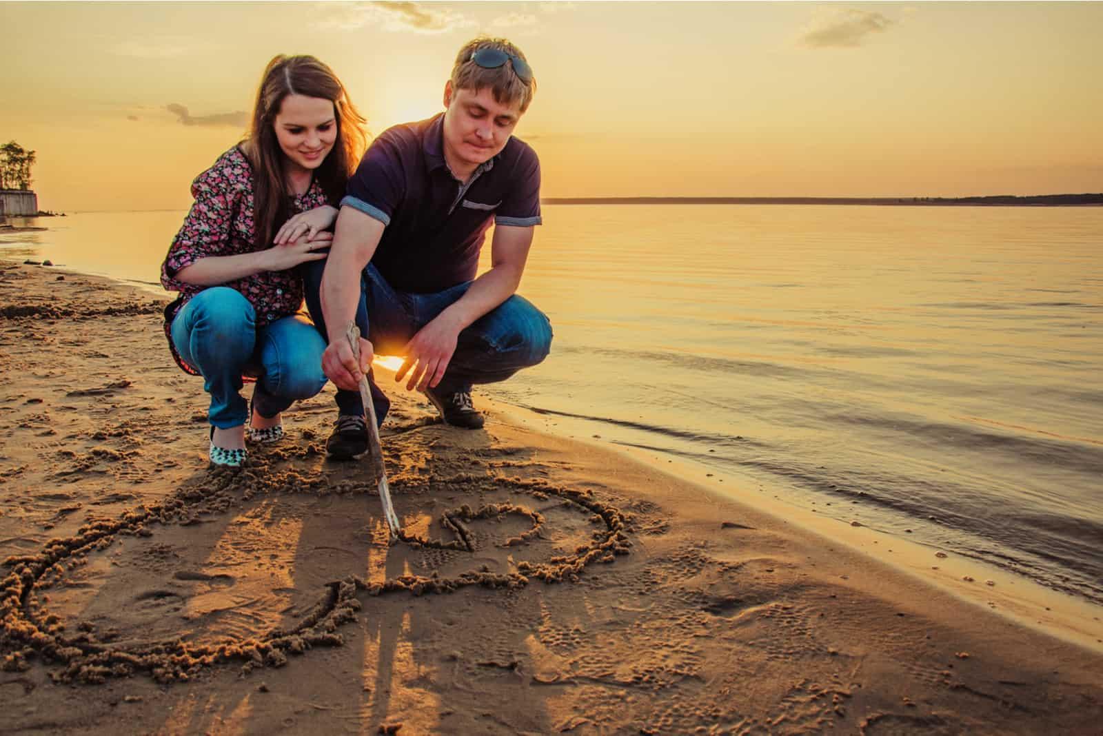 Ein verliebtes Paar zieht ein Herz an einen Sandstrand