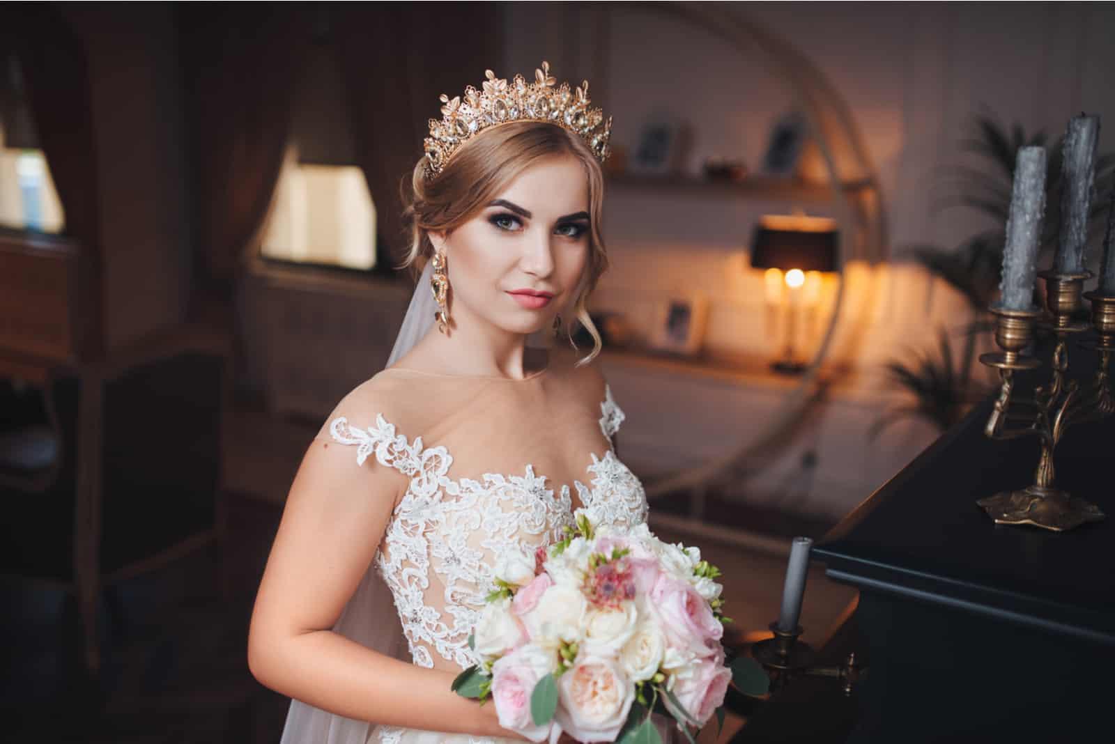 Eine blonde Braut mit einer Krone oder einem Diadem auf dem Kopf schaut in die Kamera