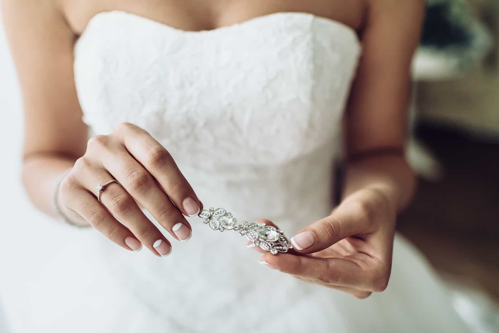 Elegante Braut, die silberne Ohrringe hält
