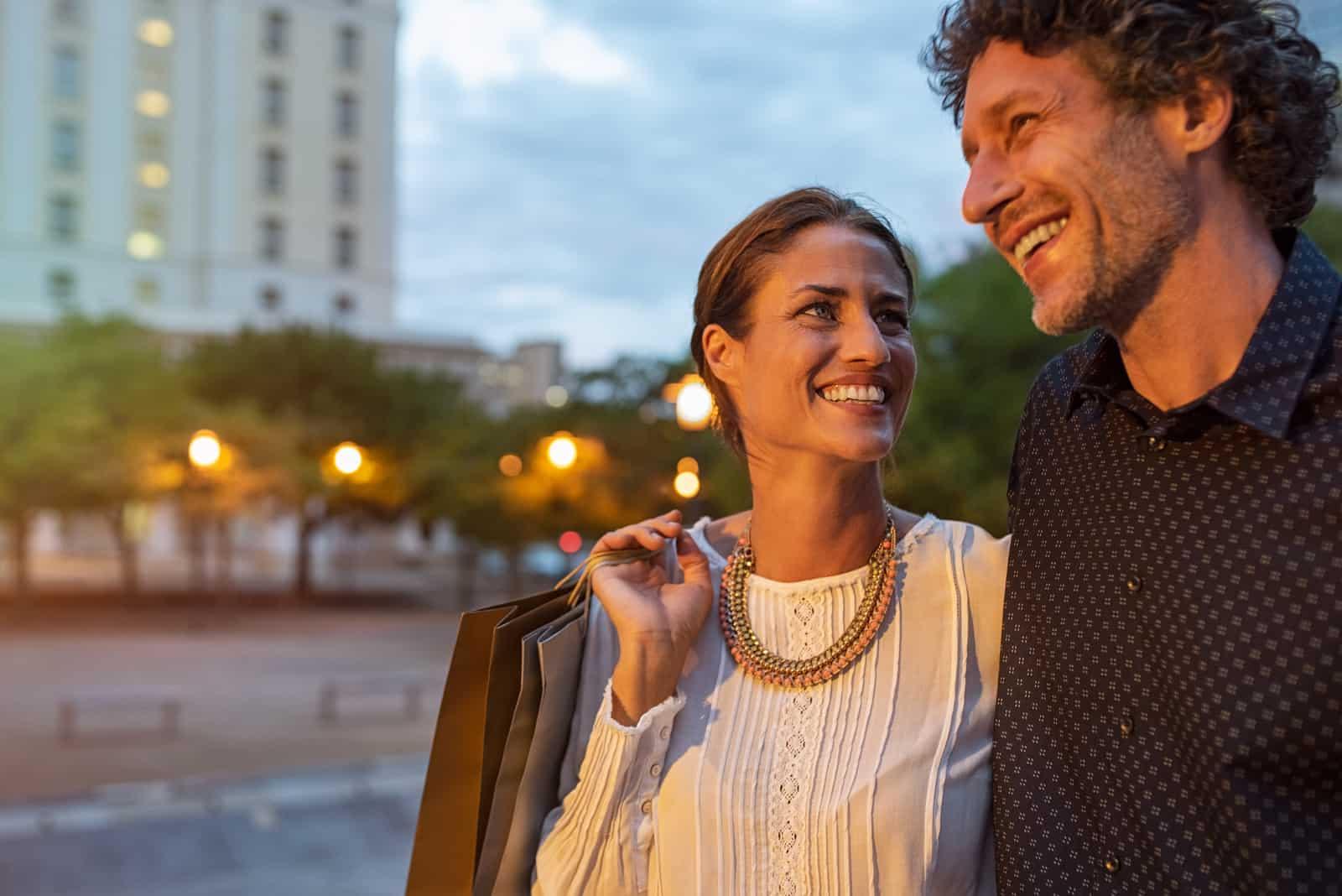 Frau, die abends mit ihrem Mann Einkaufstaschen trägt