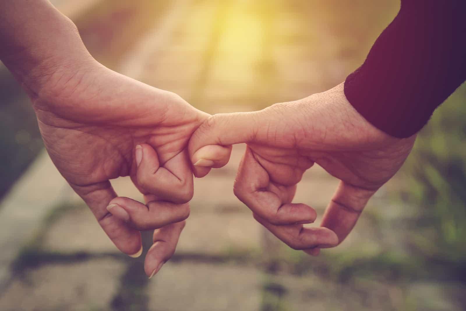Glückliches Paar, das Hände als ewige Liebe zusammenhält