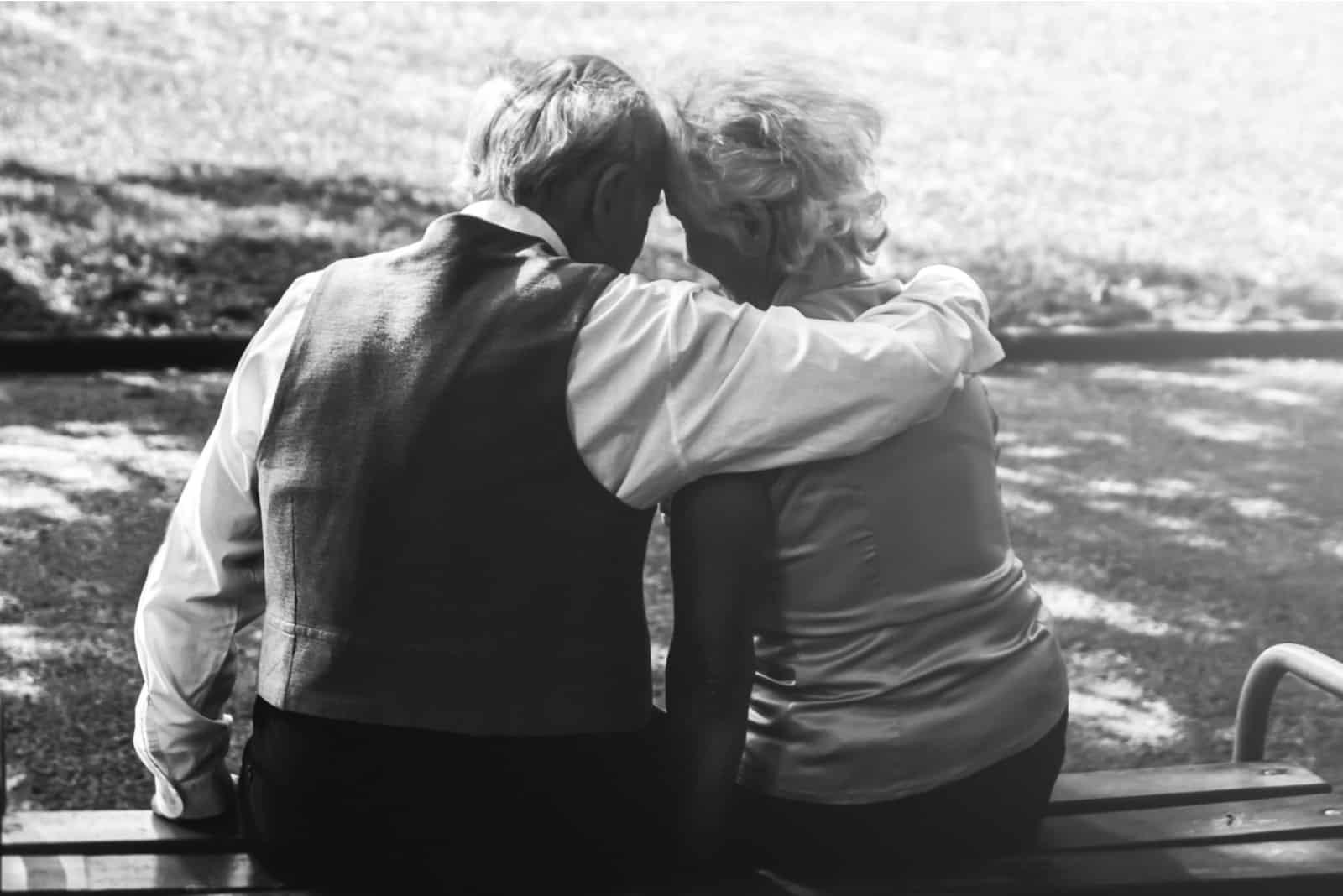 Glückliches älteres Paar, das auf der Bank sitzt
