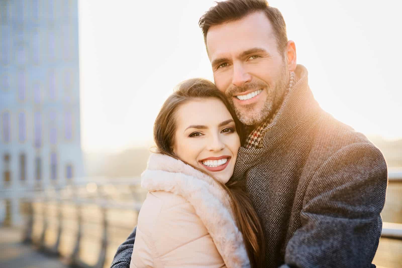 Glückliches Paar mittleren Alters, das lächelt und in die Kamera schaut, während es sich umarmt