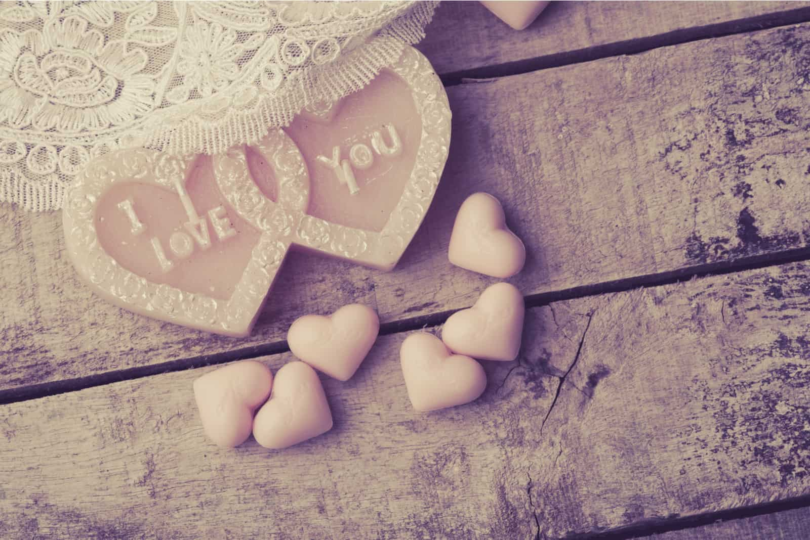 Herz aus Kerzen und Seife auf Holzhintergrund