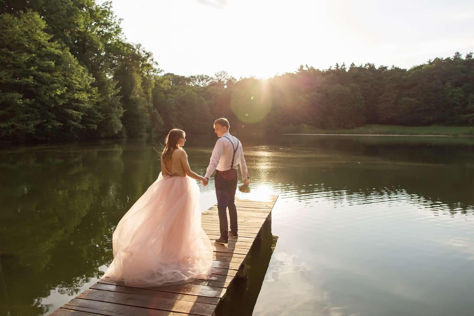 Hochzeitspaar, das auf Brücke nahe See geht