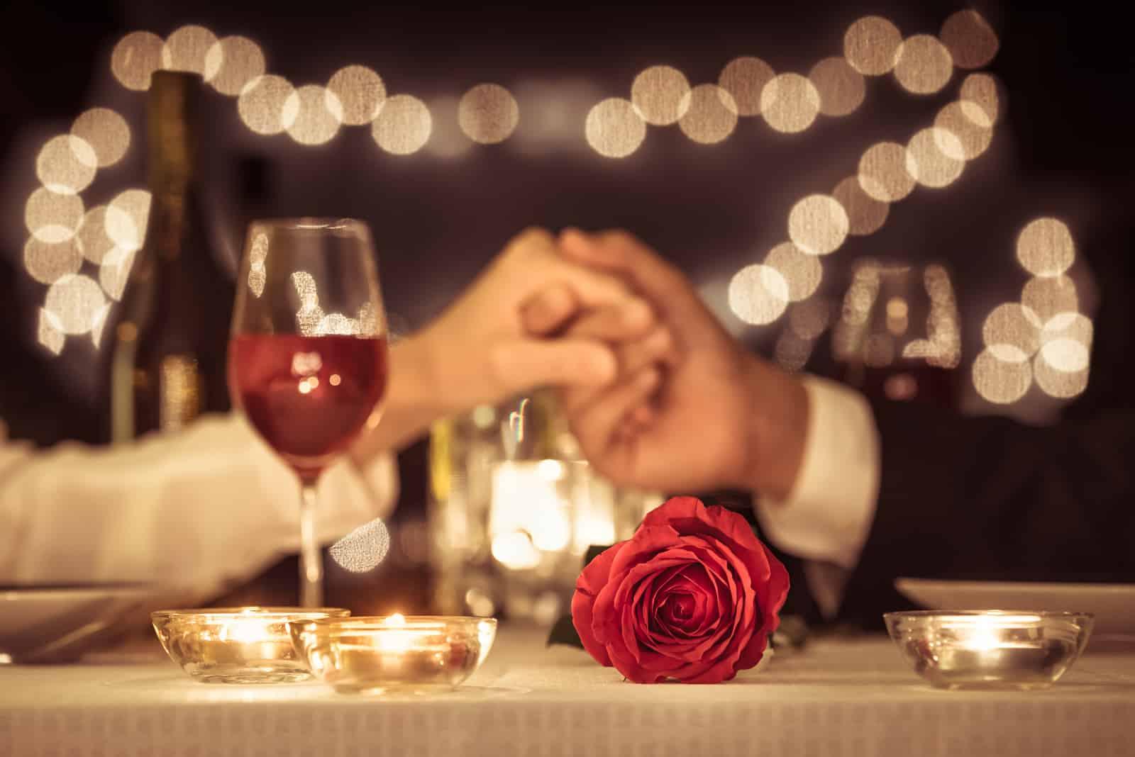Paar, das Hände hält, die ein romantisches Abendessen haben