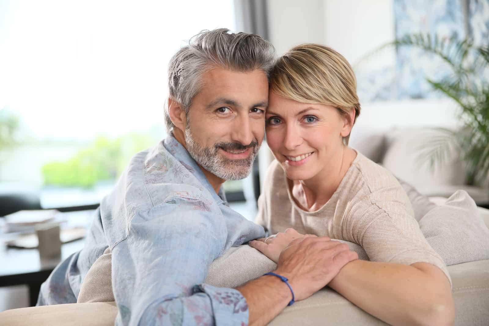 Paar mittleren Alters, das sich auf dem Sofa zu Hause entspannt