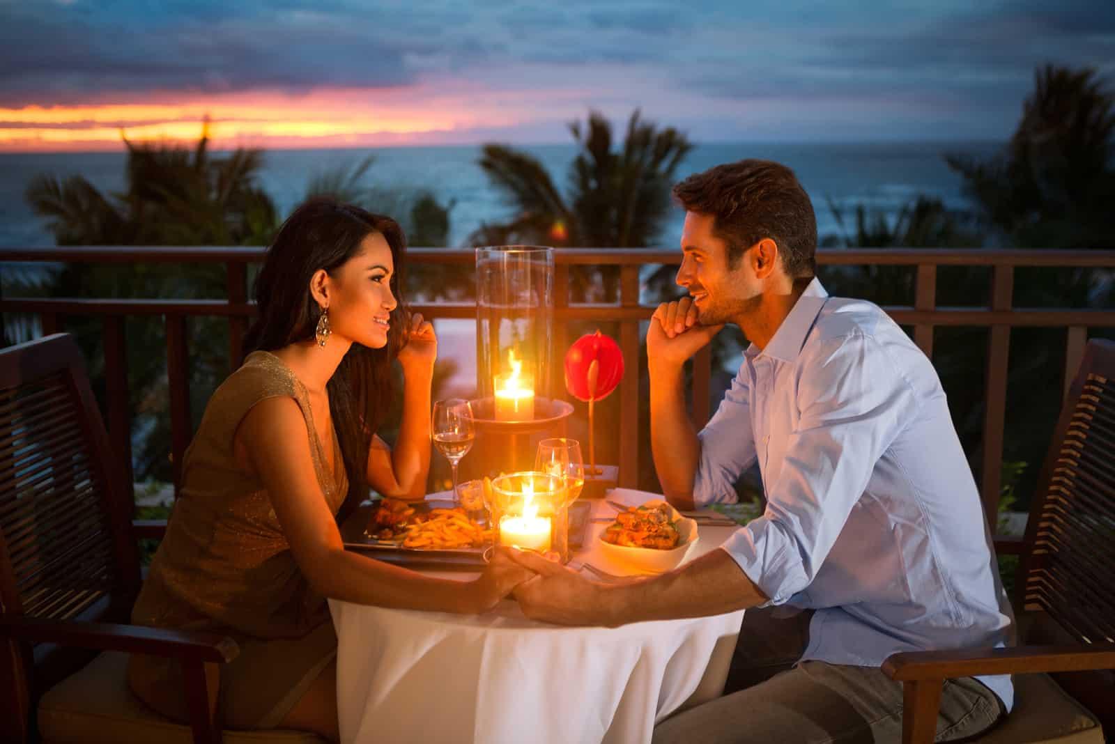 Romantisches Paar essen mit Sonnenuntergang und Kerzenlicht zu Abend