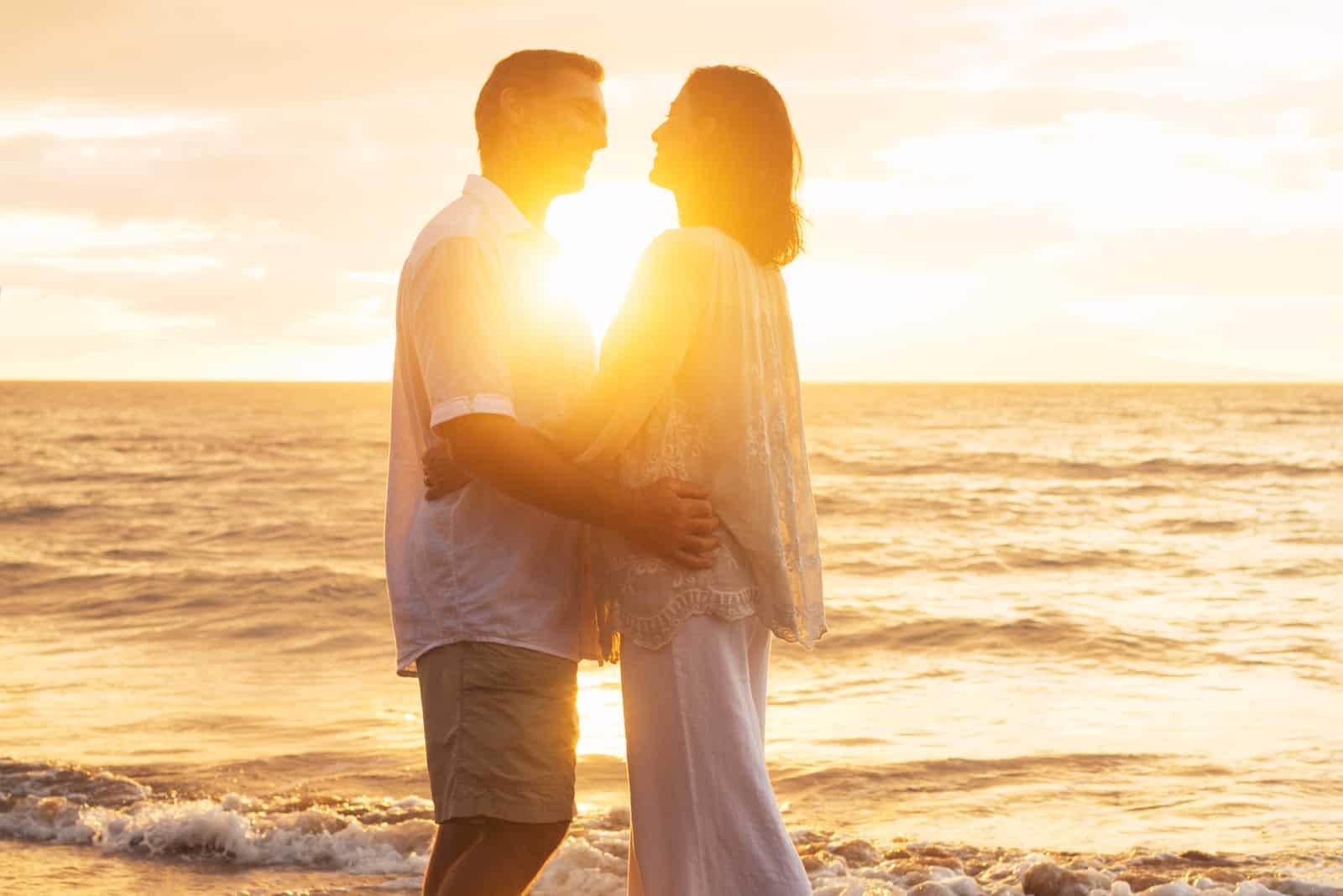 Romantisches reifes Paar, das bei Sonnenuntergang küsst