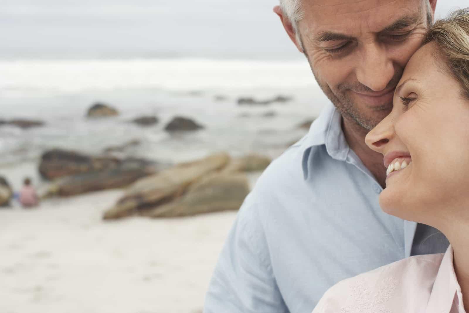 am Strand genießt und umarmt ein glückliches Paar