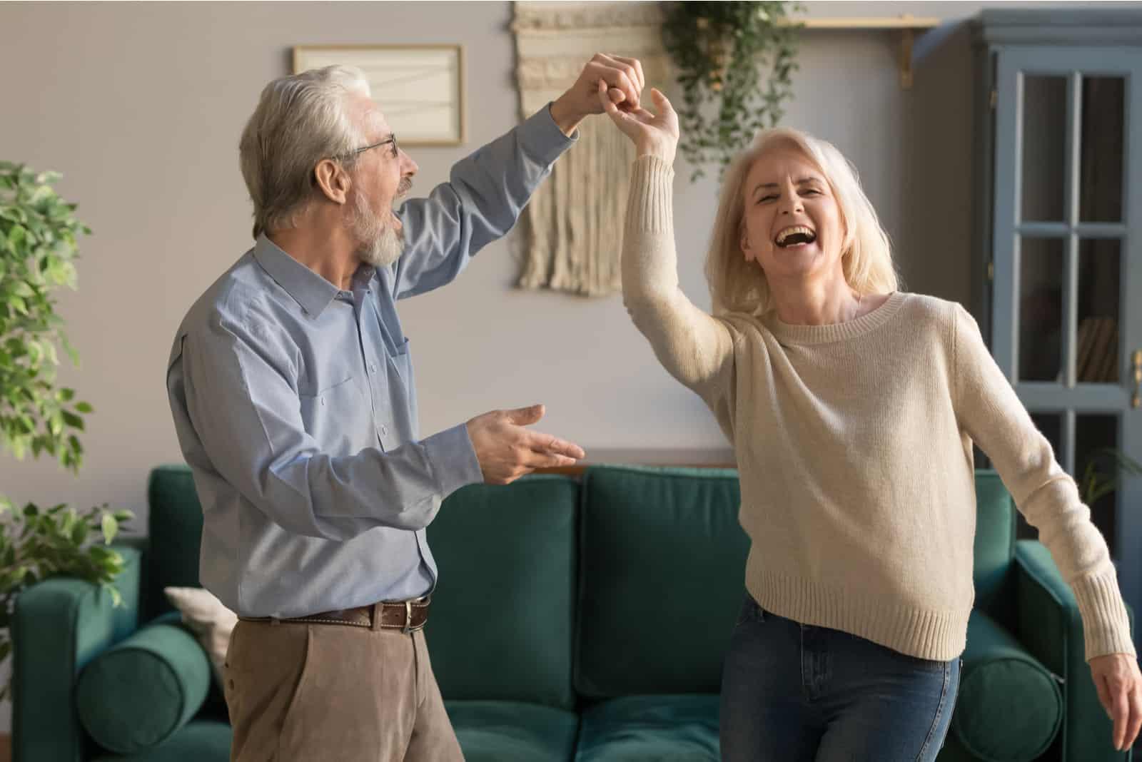 ein älteres Ehepaar tanzt im Wohnzimmer