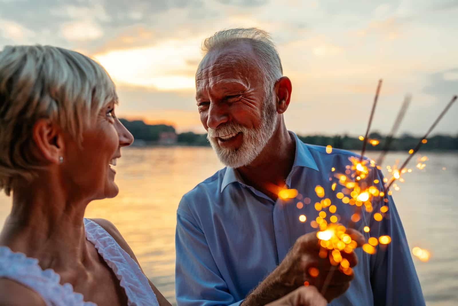 glückliches älteres Paar, das mit Wunderkerzen am Fluss feiert