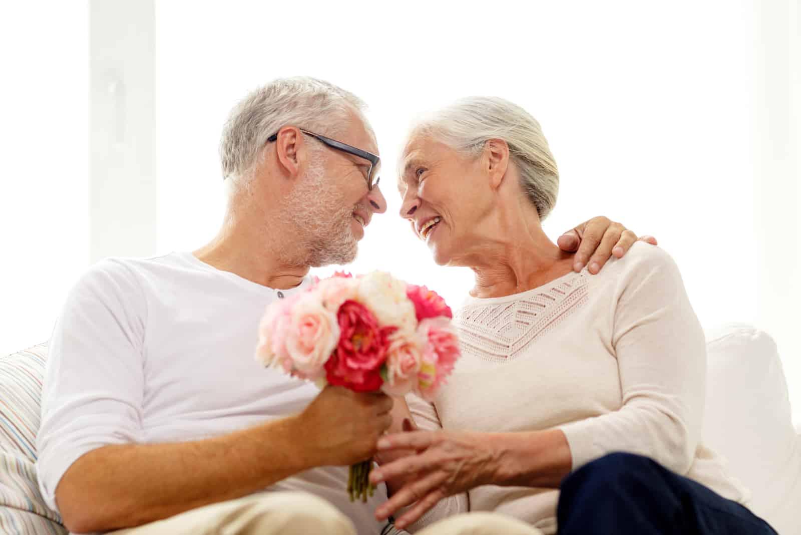 glückliches älteres Paar mit Blumenstrauß zu Hause