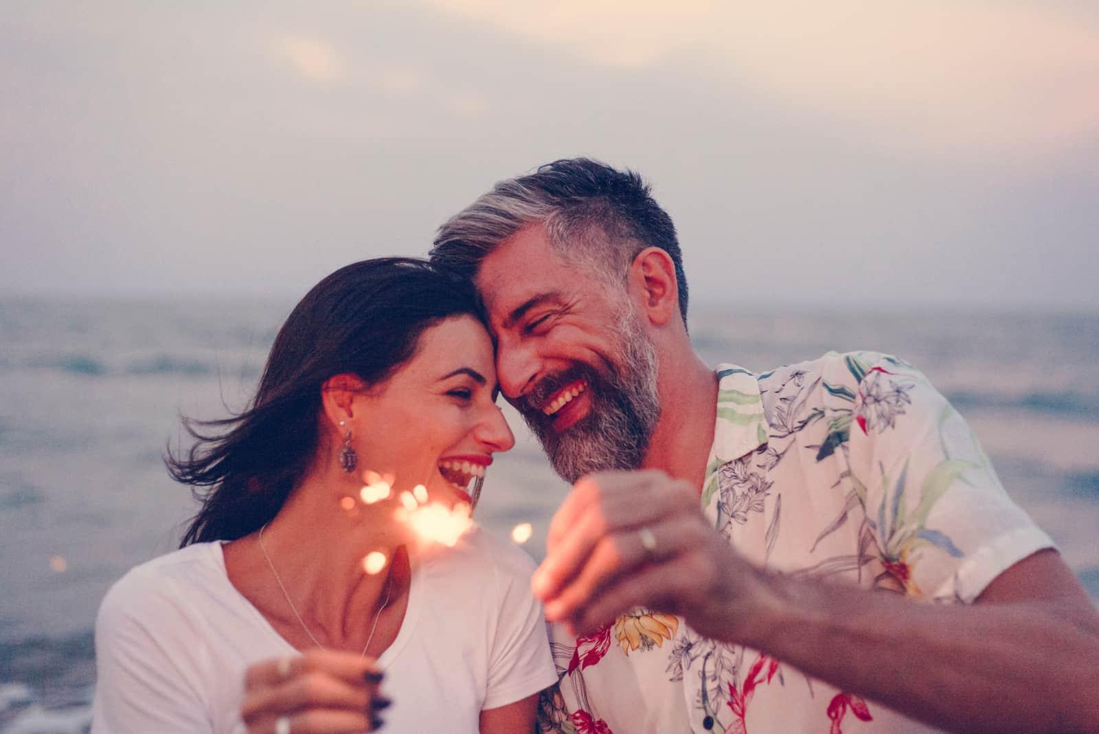 glückliches Paar, das mit Wunderkerzen am Strand feiert