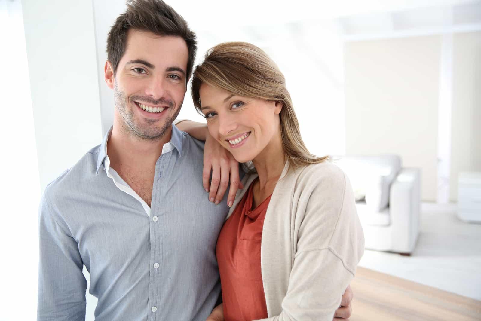 lächelndes Paar, das im zeitgenössischen Haus steht
