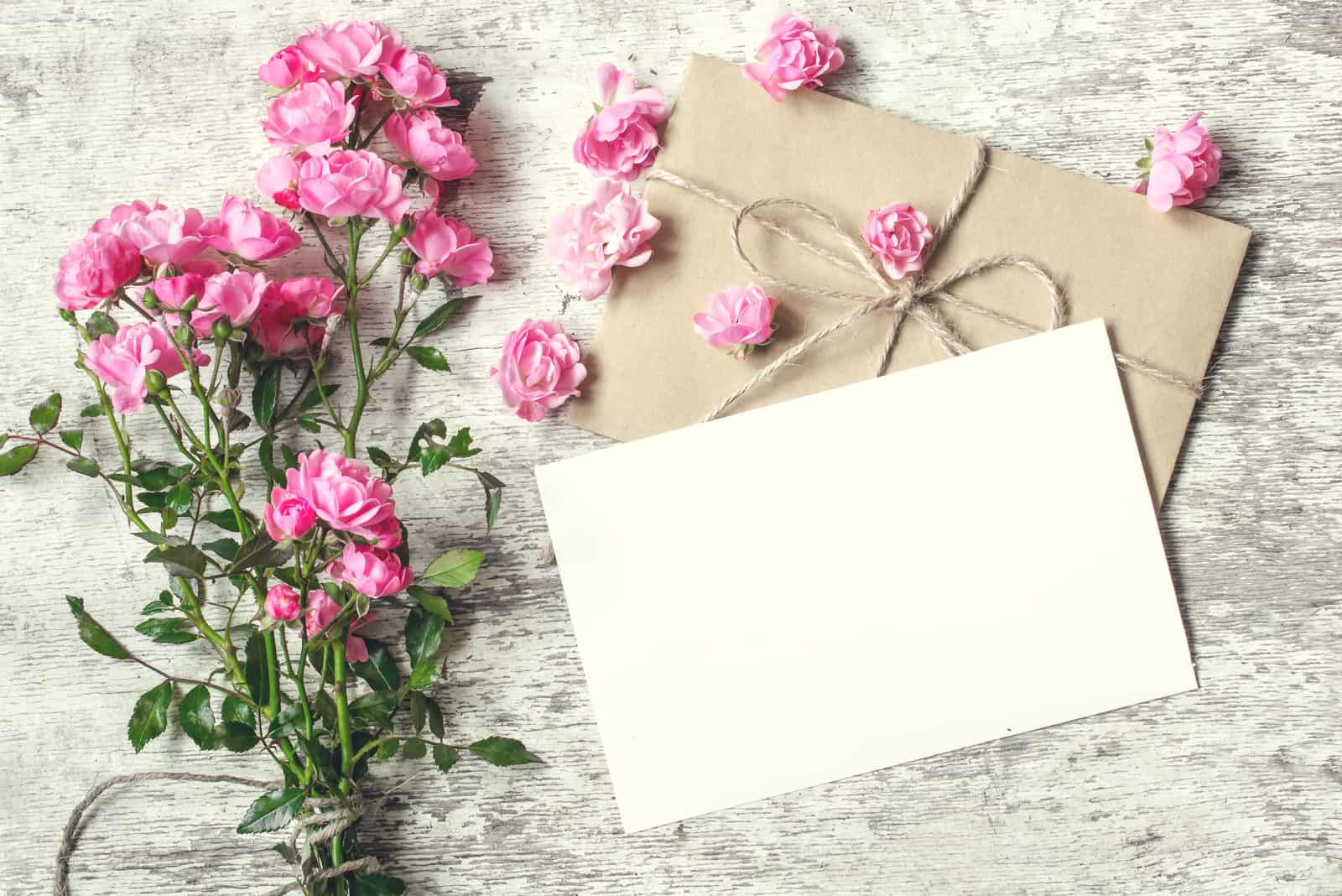 leere weiße Grußkarte mit rosa Rosenblumenstrauß