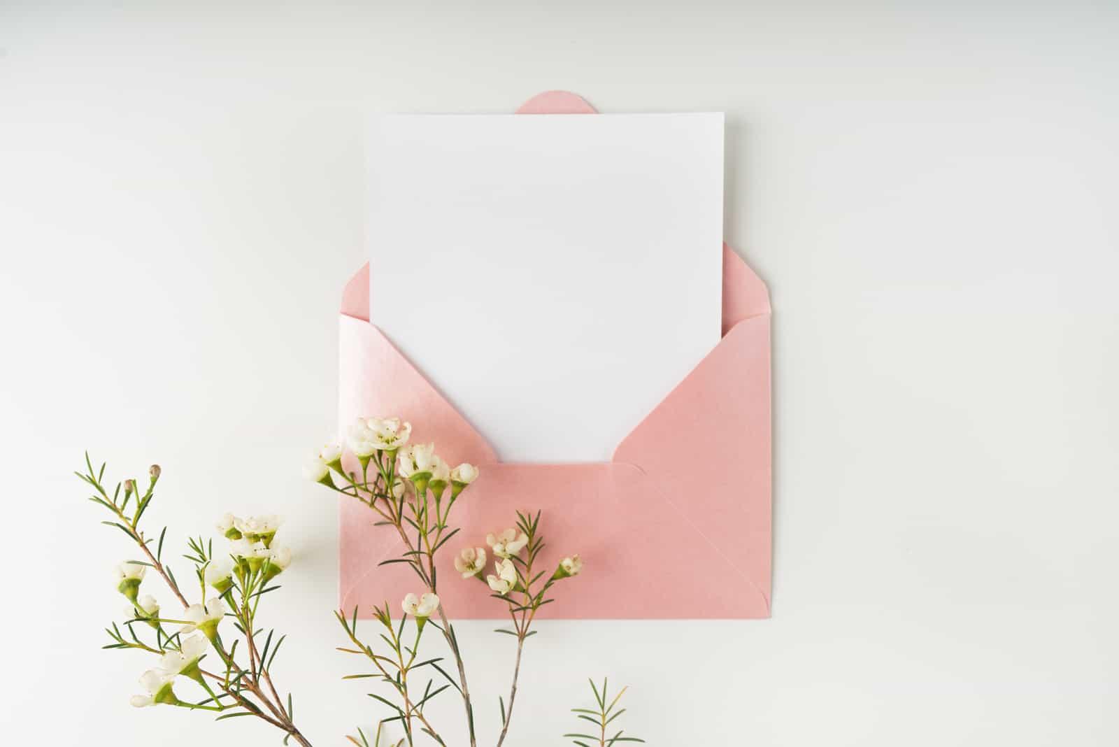 rosa Umschlag und weiße leere Karte