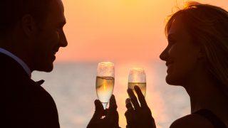 Paar bei Sonnenuntergang am Strand mit Gläsern Champagner
