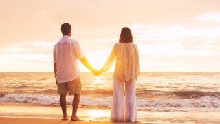 Älteres Paar, das Sonnenuntergang am Strand genießt