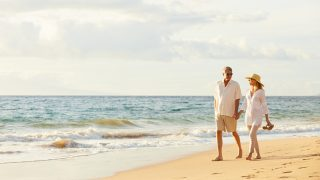 Paar mittleren Alters, das schönen Sonnenuntergangspaziergang genießt