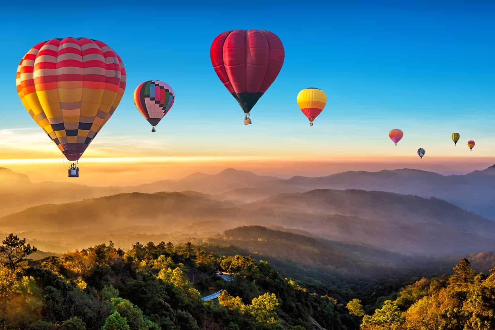 Bunte Heißluftballons, die über Berg fliegen